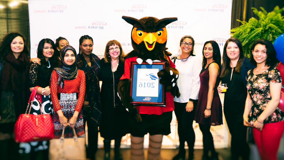 Swoop holding an award with students.